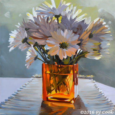 Daisy flowers in orange glass vase backlit with morning sun